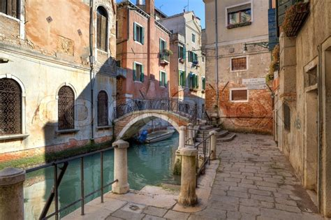 Small bridge over canal and old historic houses in Venice